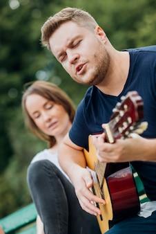 Mężczyzna na ławce gra na gitarze i śpiewa