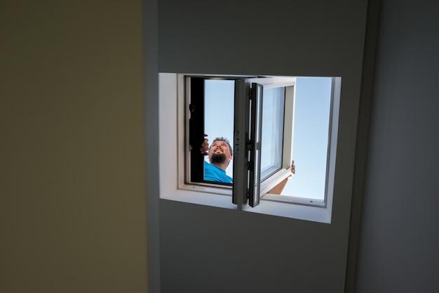 Mężczyzna na loft dachu okno indoors przegląda
