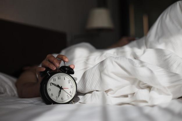 Mężczyzna na łóżku obudził się, gdy budzik pokazuje godzinę 7