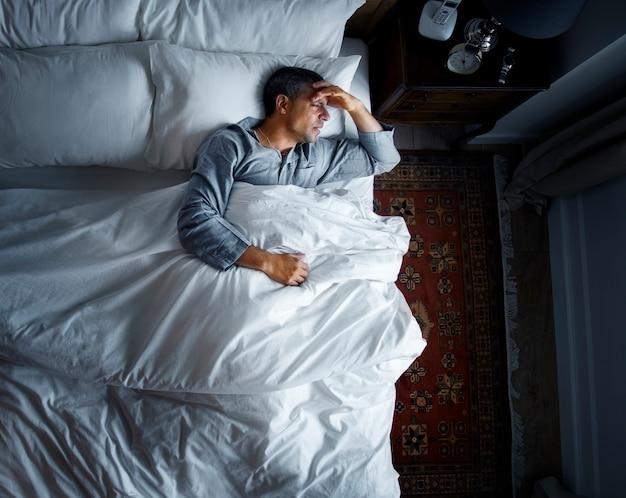 Mężczyzna na łóżku z bólem głowy