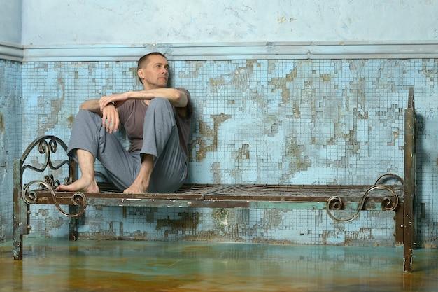 Mężczyzna na metalowym zardzewiałym łóżku w więzieniu