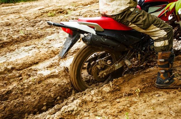 Mężczyzna na motocyklu jedzie przez błoto