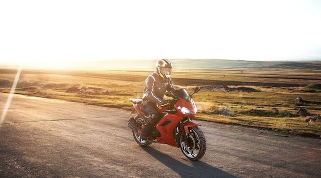Mężczyzna na motocyklu w asfaltowej drodze o zachodzie słońca