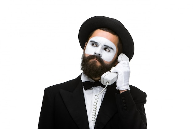 Mężczyzna na obrazie mime trzyma słuchawkę.
