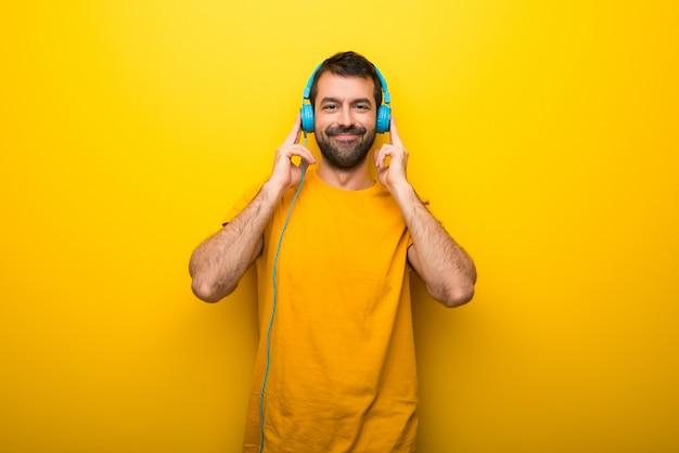 Mężczyzna na odosobnionym wibrującym żółtym kolorze słucha muzyka z hełmofonami