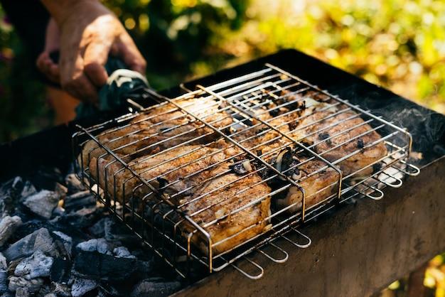 Mężczyzna na pikniku na łonie natury gotuje szaszłyk, mięso na piecyku i ogień