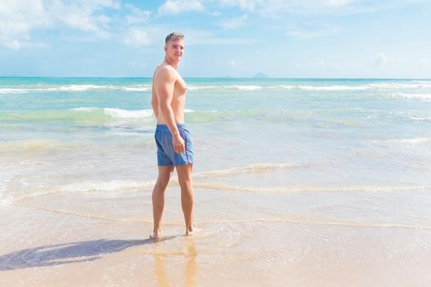 Mężczyzna na plaży, młody, wysportowany, szczupły facet mężczyzna pływa w morzu, spacery po piasku