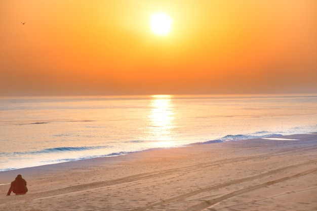 Mężczyzna na plaży o zachodzie słońca z długą linią brzegową, słońcem i dramatycznym niebem