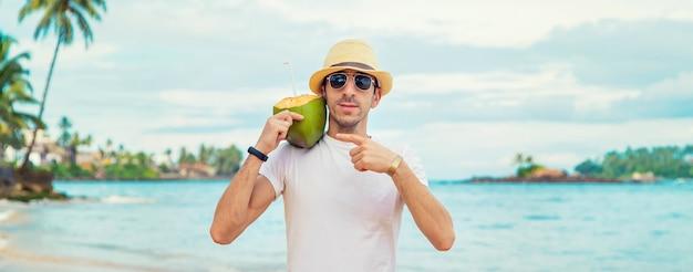 Mężczyzna na plaży pije kokos