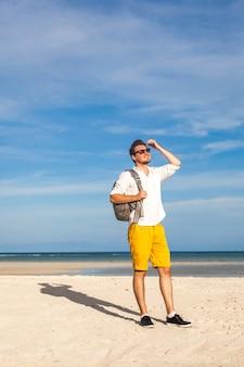 Mężczyzna na plaży uśmiechnięty i ubrany w jasny strój hipster