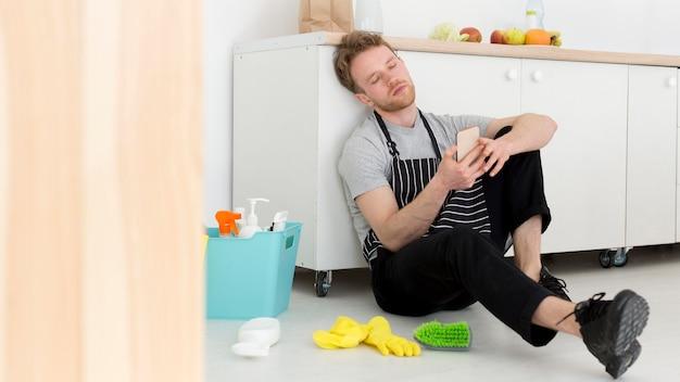 Mężczyzna na przerwie od czyszczenia sprawdza mobilnego