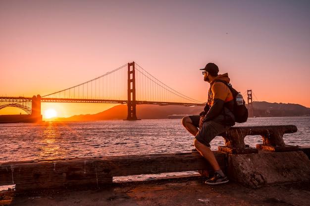 Mężczyzna na red sunset w golden gate w san francisco. stany zjednoczone