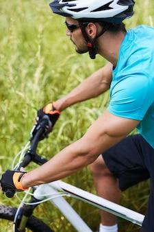 Mężczyzna na rowerze po łące
