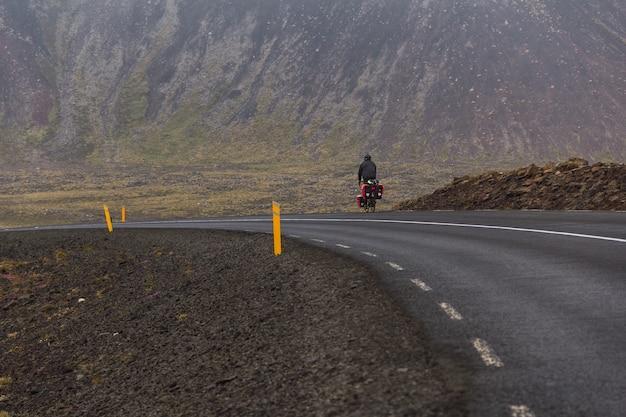 Mężczyzna na rowerze po utwardzonej drodze w islandii.