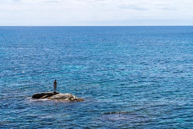 Mężczyzna na skale na środku morza.