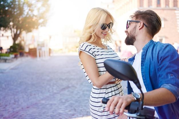 Mężczyzna na skuterze flirtuje z dziewczyną