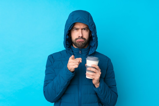 Mężczyzna na sobie kurtkę zimową i trzymając kawę na wynos na pojedyncze niebieskie ściany sfrustrowany i wskazując na przód