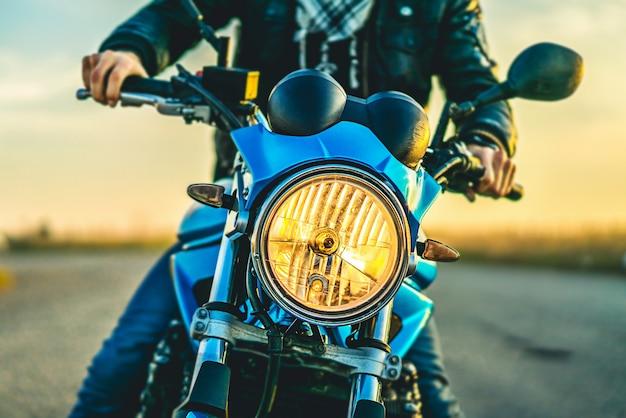 Mężczyzna na sportowym motocyklu plenerowym na drodze