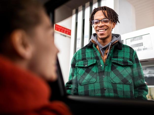 Mężczyzna na stacji benzynowej z samochodem
