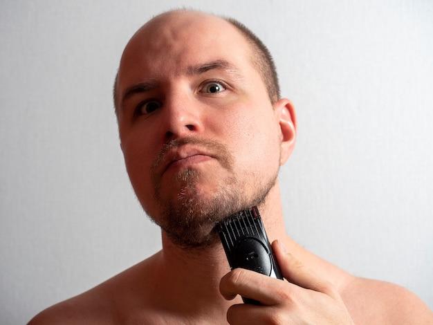 Mężczyzna na szarym tle goli brodę elektryczną maszynką do golenia. patrzy w kamerę, przycinając włosy. męska uroda i pielęgnacja w domu. ostre światło
