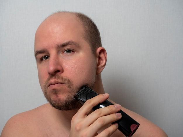 Mężczyzna na szarym tle goli brodę elektryczną maszynką do golenia. patrzy w kamerę, przycinając włosy. męska uroda i pielęgnacja w domu.