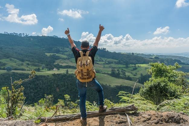 Mężczyzna na szczycie góry z rękami do góry