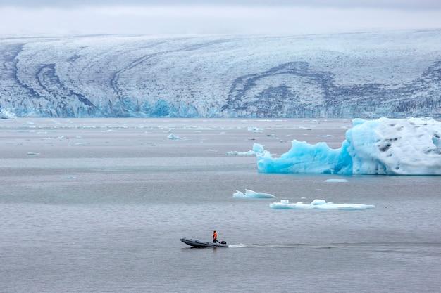 Mężczyzna na szybkiej łodzi motorowej płynącej po lagunie lodowcowej w islandii