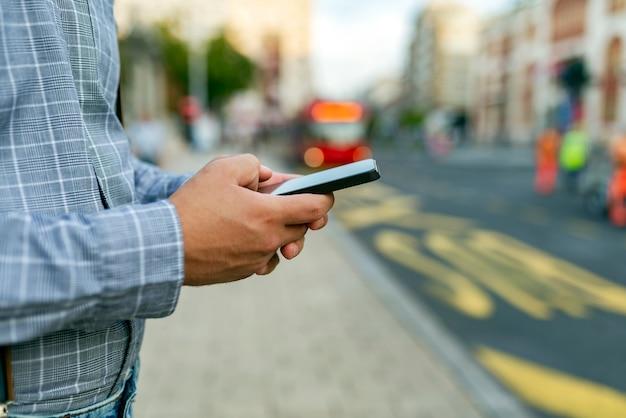 Mężczyzna na ulicy z telefonem w rękach