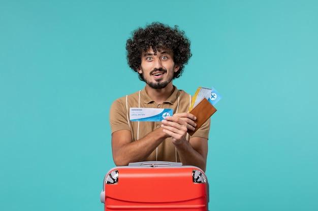 Mężczyzna na wakacjach trzymający bilet i czytający na niebiesko