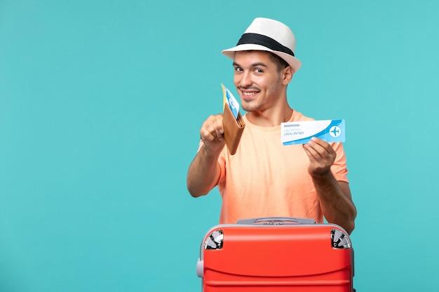 Mężczyzna na wakacjach trzymający bilet i uśmiechający się na niebiesko