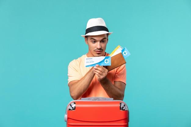 Mężczyzna na wakacjach trzymający bilety i sprawdzający na niebiesko