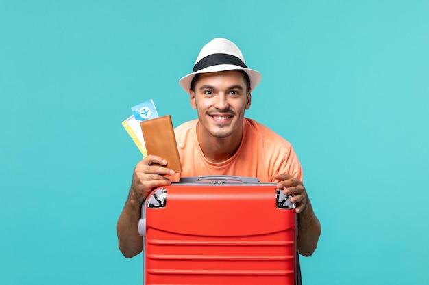 Mężczyzna na wakacjach trzymający bilety i uśmiechający się na niebiesko