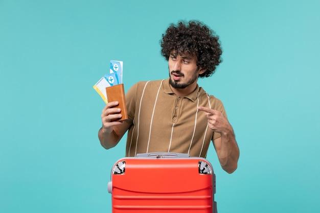 Mężczyzna na wakacjach trzymający bilety na jasnoniebieskim
