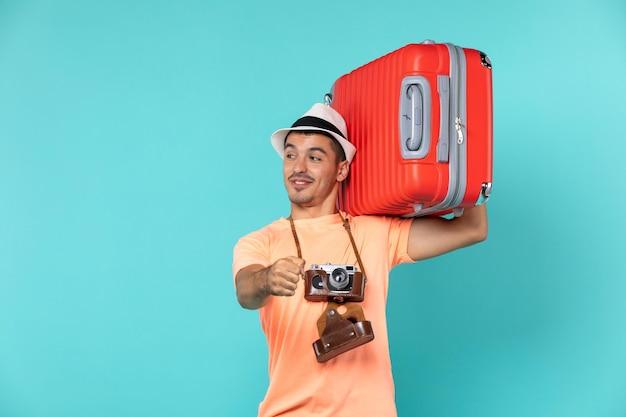 Mężczyzna na wakacjach trzymający dużą czerwoną walizkę na jasnoniebieskim kolorze