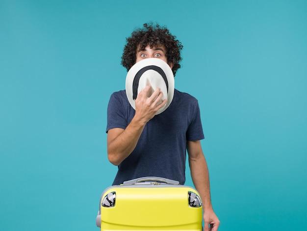 Mężczyzna na wakacjach trzymający kapelusz na niebieskiej podłodze lato podróż wakacje morze podróż samolot