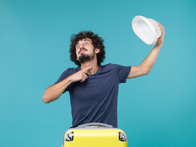 Mężczyzna na wakacjach trzymający kapelusz na niebieskiej podłodze podróż podróż letnie wakacje morski samolot