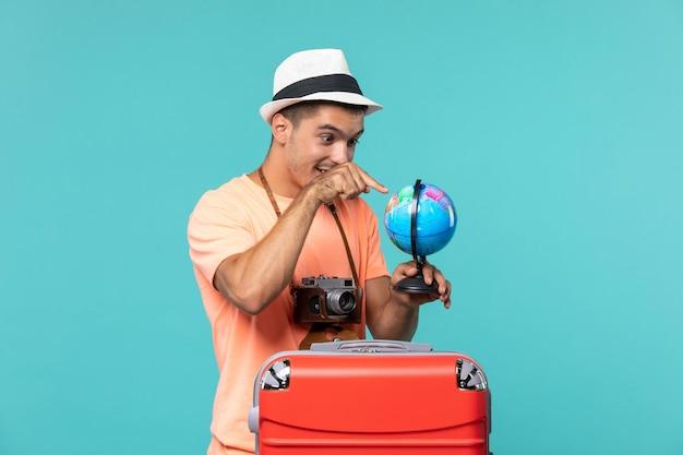Mężczyzna na wakacjach trzymający kulę ziemską i robiący zdjęcia aparatem na niebiesko