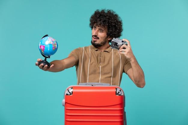 Mężczyzna na wakacjach trzymający małą kulę ziemską i aparat na jasnoniebieskim tle