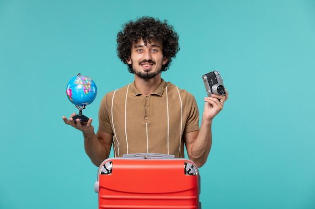 Mężczyzna na wakacjach trzymający małą kulę ziemską i aparat na niebiesko