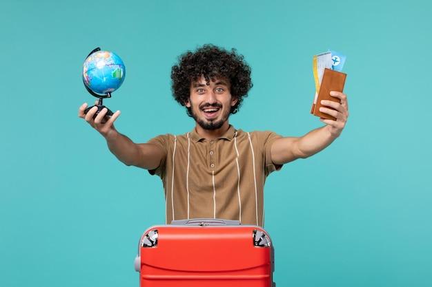 Mężczyzna na wakacjach trzymający małą kulę ziemską i bilet na jasnoniebieskim tle