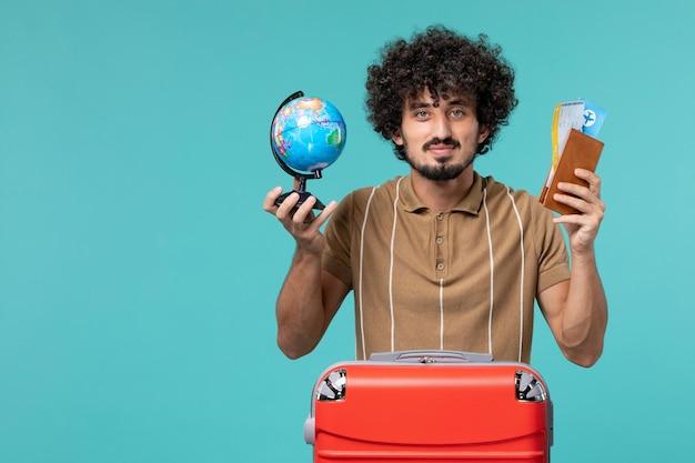 Mężczyzna na wakacjach trzymający małą kulę ziemską i bilet na niebiesko