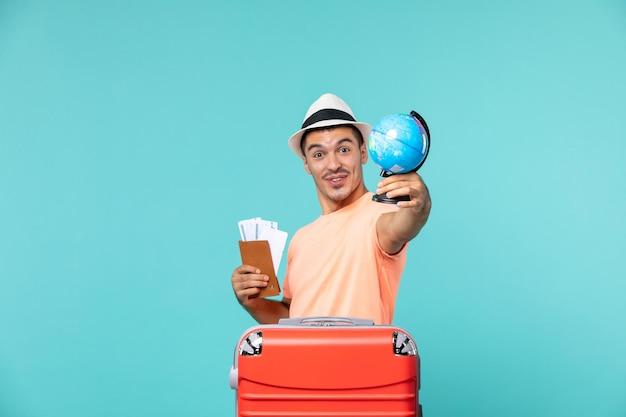 Mężczyzna na wakacjach trzymający małą kulę ziemską i bilety na jasnoniebieskim kolorze