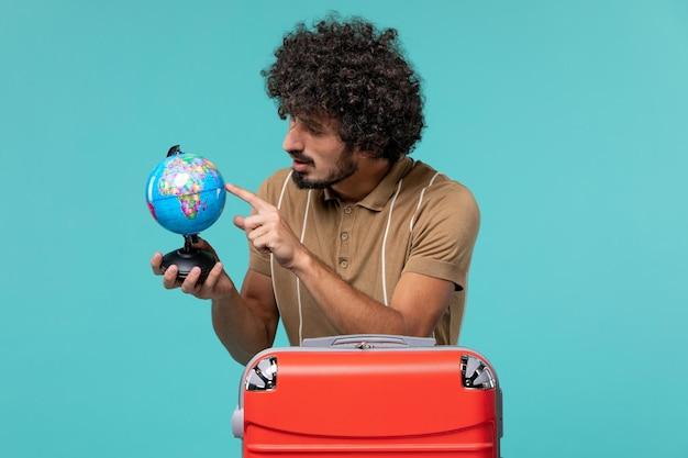 Mężczyzna na wakacjach trzymający małą kulę ziemską na jasnoniebieskim