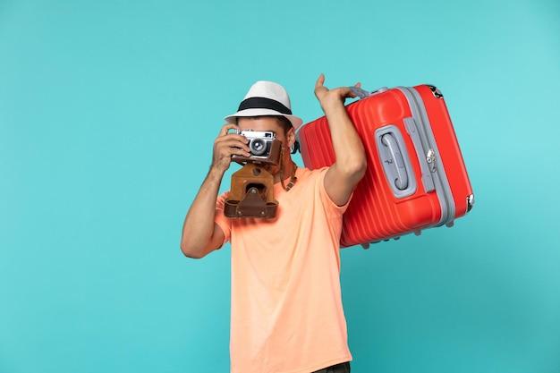 Mężczyzna na wakacjach z czerwoną walizką i aparatem robiącym zdjęcia na niebiesko
