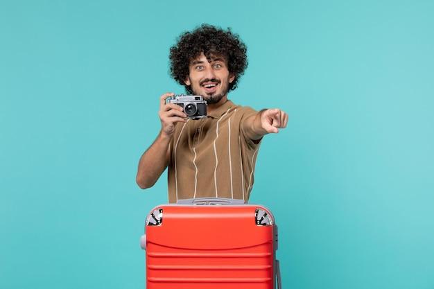 Mężczyzna na wakacjach z czerwoną walizką robi zdjęcia aparatem na jasnoniebiesko