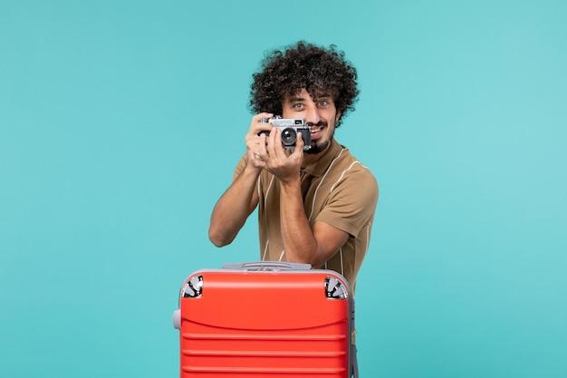 Mężczyzna na wakacjach z czerwoną walizką robi zdjęcia aparatem na niebiesko