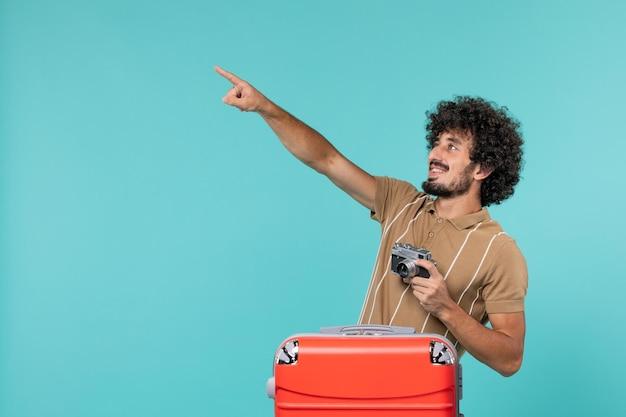Mężczyzna na wakacjach z dużą czerwoną walizką robi zdjęcia aparatem na jasnoniebieskim kolorze