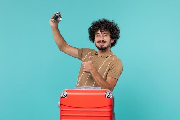 Mężczyzna na wakacjach z dużą czerwoną walizką robi zdjęcia aparatem na niebiesko