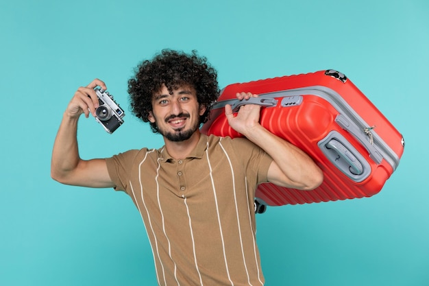 Mężczyzna na wakacjach z dużą walizką robi zdjęcia aparatem na niebiesko