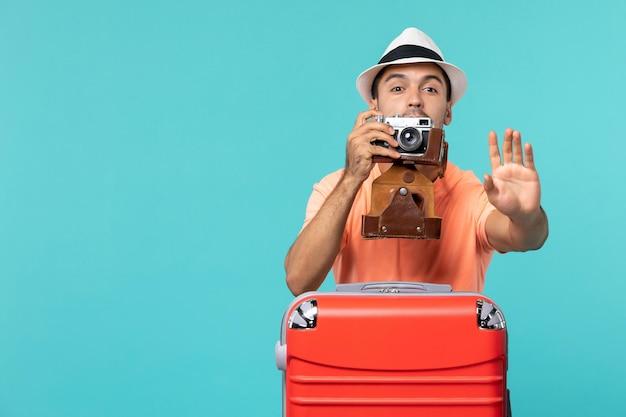 Mężczyzna na wakacjach ze swoją czerwoną walizką i aparatem na niebiesko